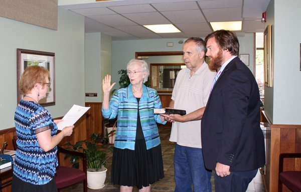 Clerk of Court Diane Deal swears in Loretta Clawson as a council member while Mayor Andy Ball and Clawson's husband L.D. look on.