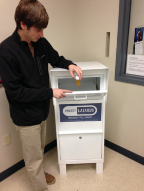 Logan Shaut, Project Lazarus of Watauga County intern demonstrates how the medication dropbox is used.