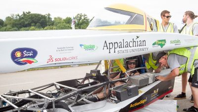 With a big smile, Lindsay Rudisill celebrates being qualified as a driver in the American Solar Challenge, as pit boss Jon Linck checks the vehicle with support from co-electrical assistant Logan Ward (who qualified as a driver earlier in the day) and business director and pit crew member Andrew Grimes.