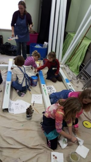 Students work together to paint peace poles.