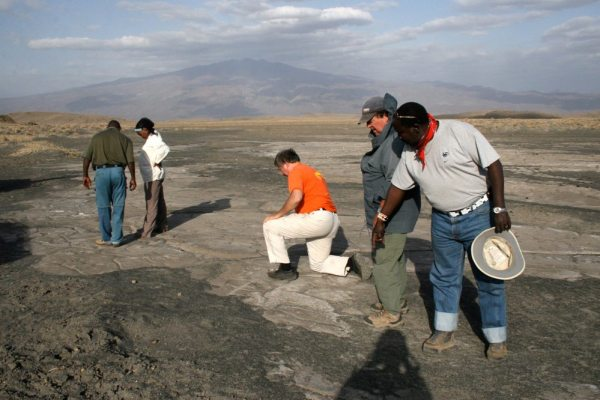 Seeing the footprints for the first time in 2008 was an emotional experience for the researchers. Jim Brett, in blue hat, and Godfrey Olle Moita, far right, point out footprints emerging from beneath the sand. Photo by Cynthia Liutkus-Pierce