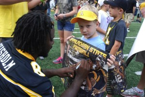 A football player signs autographs for a kid at last year's Fan Fest.