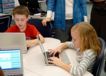 Fourth graders Eli Giles and Sophie Beach using laptops. Photo courtesy of WCS
