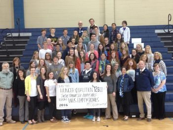 Students at Watauga High present a check for $12,600 from this year's Empty Bowls event to Elizabeth Young, director of the Hunger and Health Coalition.