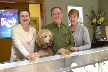 Jennie Trivette, Charlie Travis and Joy Travis are pictured with Boone the Standard Poodle behind the counter at Old World Galleries. Photo by Jessica Isaacs.