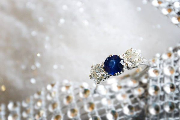 Three stone center set sapphire with old mine cut diamond side stones set in 18K white gold. Photo courtsey of Old World Galleries.