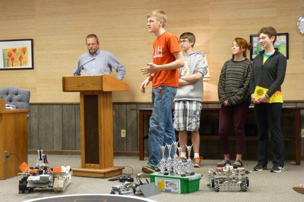 Robotics team (L to R) Levi Marland, John Boitnotte, Maddie Brown, and Alyana Arnholt; Coach and WHS science teacher Tom Brown is at far left. The team discussed their projects and recent competitions during a presentation to the Board of Education at their Monday night meeting.