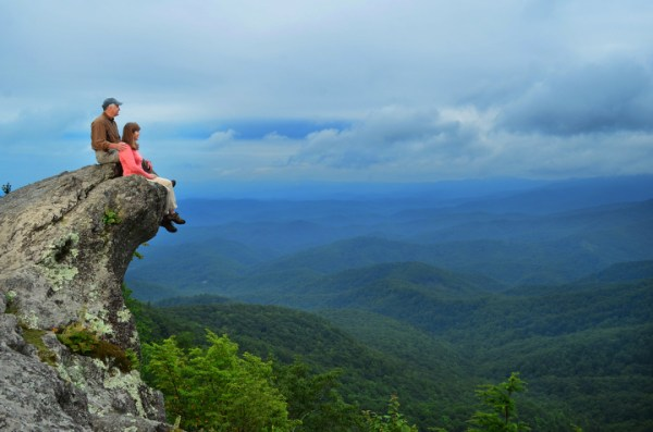A couple sits on The Blowing Rock. Photo by Todd Bush