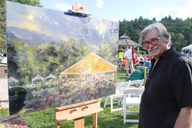 Rick Reinert works on a painting of the Symphony by the Lake during the event as the crowd enjoys the night around him. Photo by Ken Ketchie.