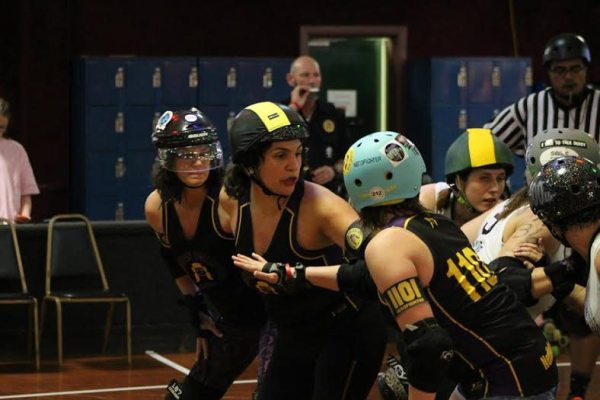Appalachian Rollergirls, Nerdfighter (right), Coco Janel (middle) and Snatch n Bent (right) blocking the Rogue Rollergirls.  Courtesy of Kevin Gordon, ARG photographer