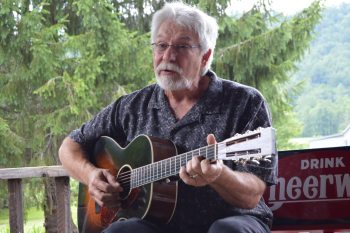 Charles Welch, a longtime friend of Doc Watson, plays a tune on the porch at the Mast Store in Valle Crucis during a press conference for MusicFest 'N Sugar Grove. Photo by Jessica Isaacs.