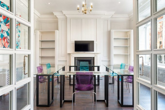 a white meeting room is filled with natural light coming from a large window on one of the walls. There is a large glass u-shaped table in the centre of the room that has purple and blue plastic chairs placed around it. Hanging from the ceiling is a small chandelier and there is a HD screen mounted on the white walls above a fireplace.