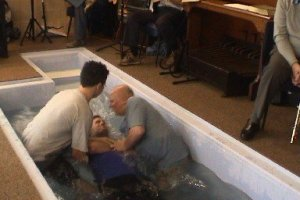 A man being baptised by two church elders in the baptismal pool at the church