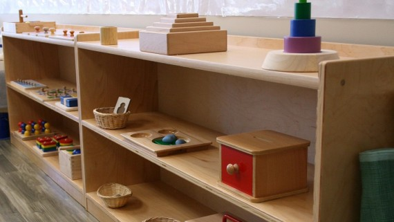Montessori learning materials placed on a bookshelf low enough for toddlers to reach