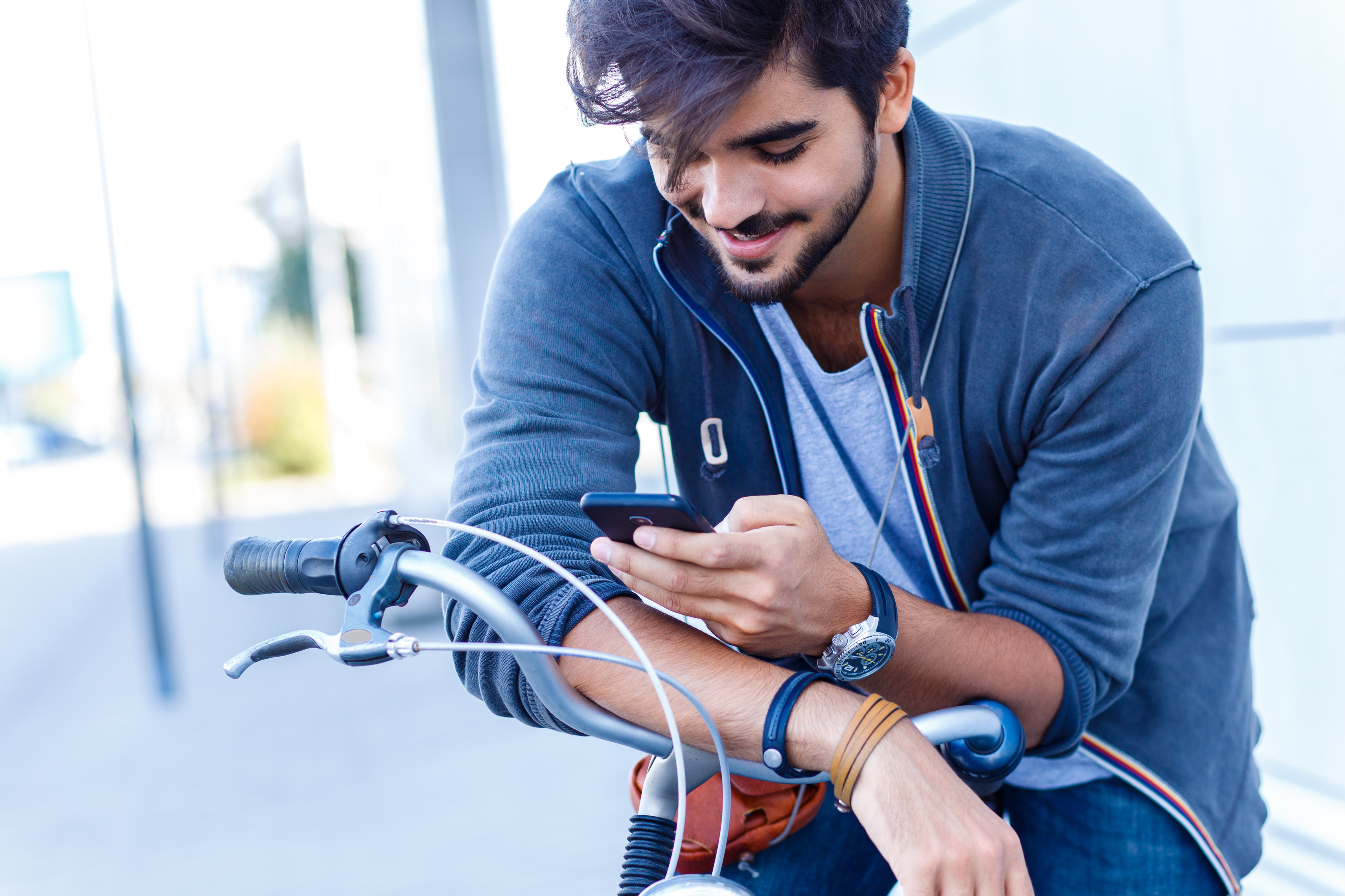 Young handsome guy on a bicycle looking at mobile phone.