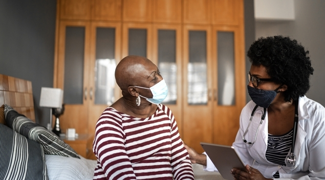 Doctor talking to patient in mask