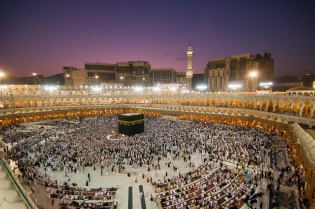Muslim pilgrims circumambulate the Kaaba at dawn