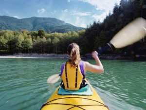 Woman kayaking, swinging paddle in air, blurred motion, rear view