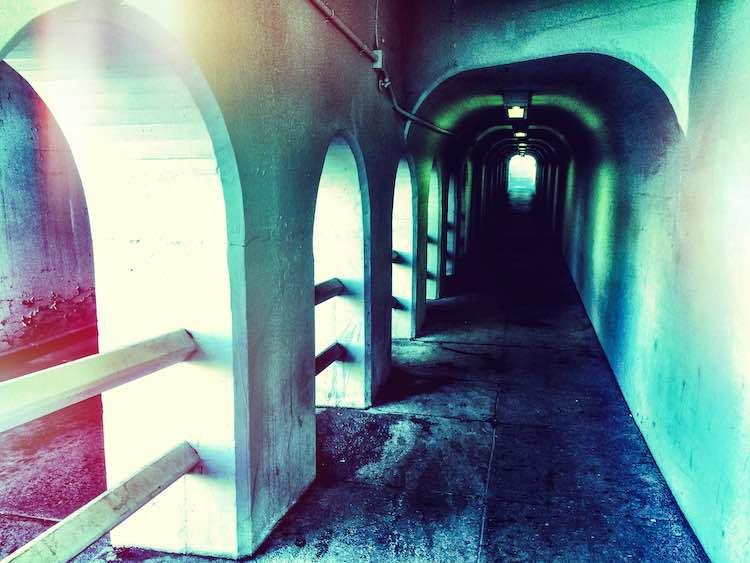 Dark pedestrian tunnel next to a roadway