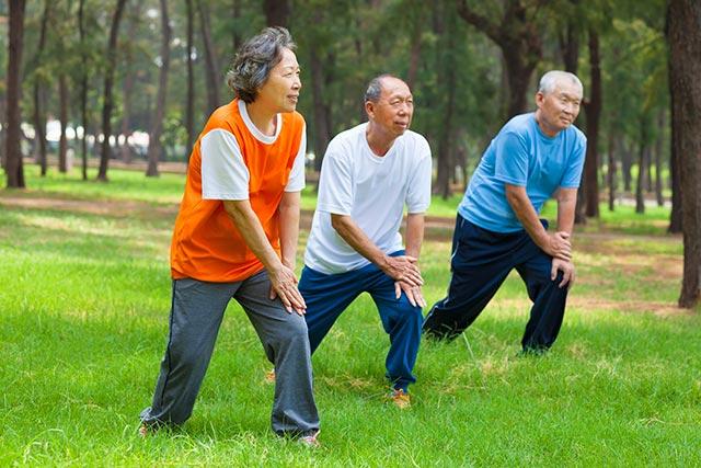 Older people exercising in groups outdoors.