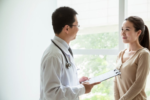 a doctor advising a young woman about the HPV vaccine