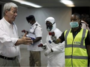 Nigerian port health officials using a thermometer on a worker at the arrivals hall of Murtala Muhammed International Airport in Lagos Source: Business Standard