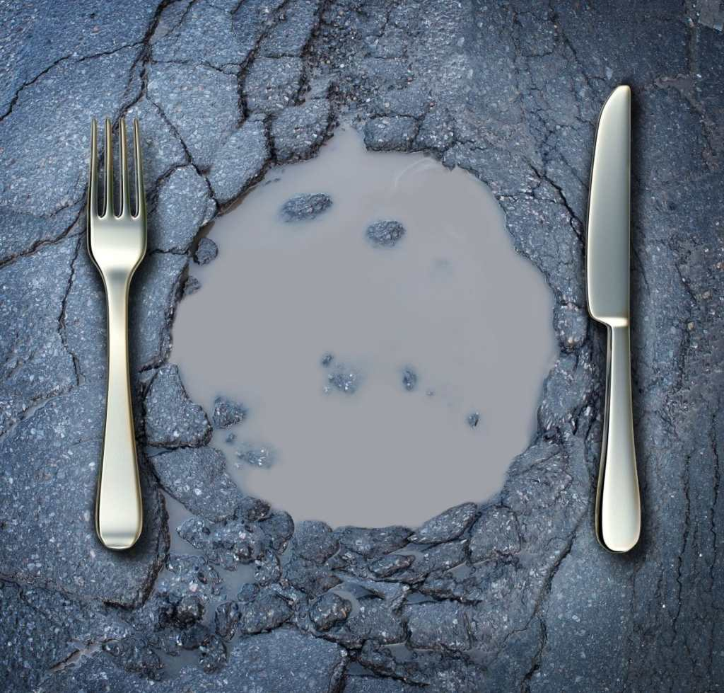 malnutrition 20948537 - poverty and hunger concept with a fork and knife on a broken asphalt road shaped as a dinner plate as a social problem of food shortage hardships caused by financial distress or natural disaster resulting in living poor on the streets as a health risk