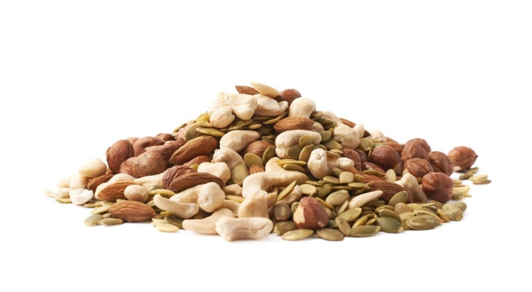 Stock Photo - Pile of multiple nuts and seeds isolated over the white background