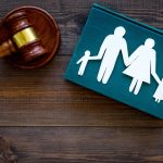 Family law, surrogacy, family right concept. Child-custody concept. Family with children cutout near court gavel on dark wooden background top view.