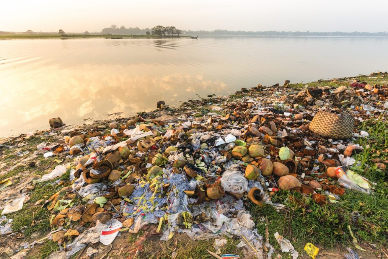 Rubbish pollution with food waste, plastic and other packaging stuffs on the bank of the Taungthaman lake near U Bein bridge in Myanmar (Burma)