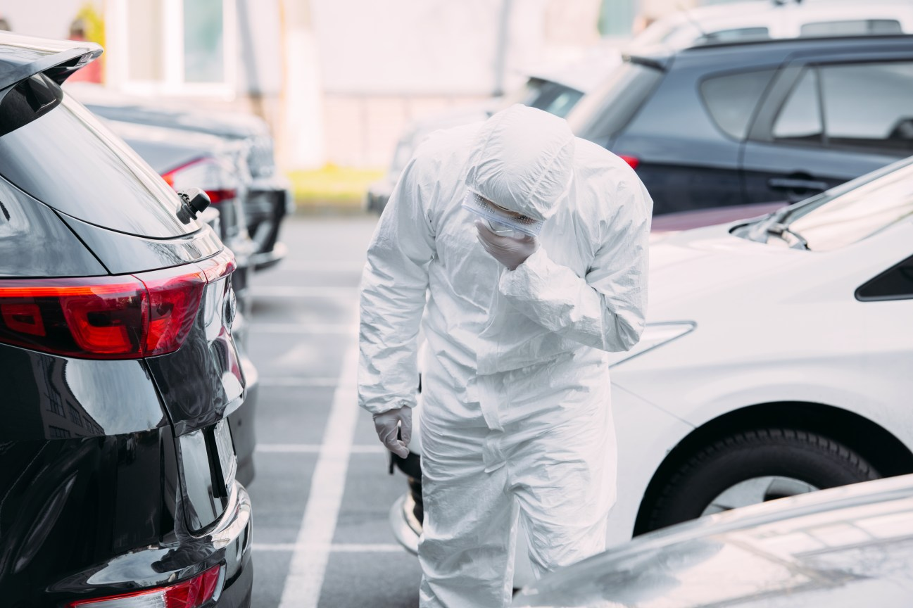 asian epidemiologist in hazmat suit and respirator mask inspecting vehicles on parking lot. Coronavirus pandemic illustration.