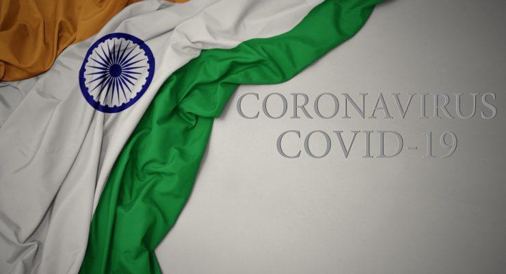 waving colorful national flag of india on a gray background with text coronavirus covid-19 . concept.. COVID-19 cases in India illustration. Indian COVID-19 cases concept. Cases of COVID-19 crisis in India concept. Image credit: luzitanija / 123rf