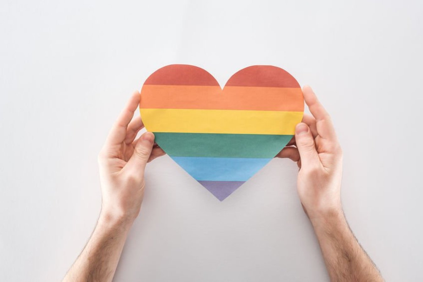 partial view of man holding paper rainbow colored paper heart on grey background, lgbt concept. bisexuality concept.