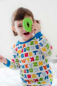 An infant playing with a letter toy.