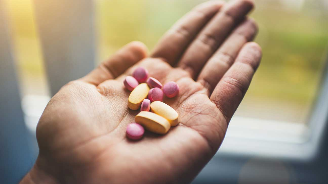 Hand Holding Yellow and Pink Pills