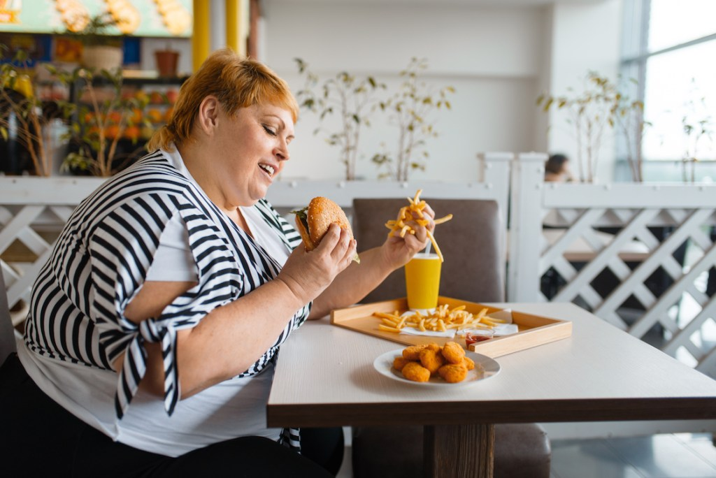 Woman eating unhealthy food and drink that damages brain health