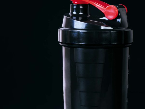 Black plastic fitness shaker on black background