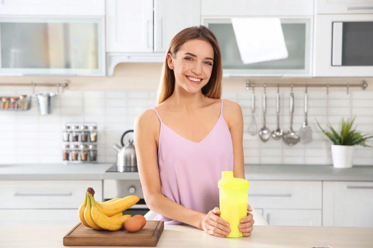 Donna in cucina con un frullato in mano
