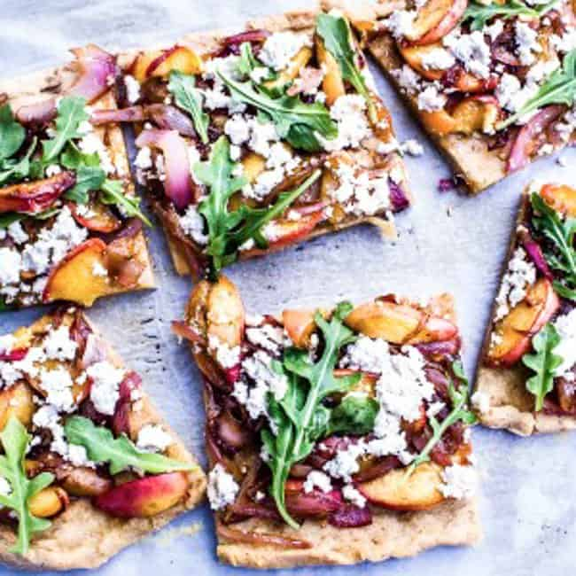 caramelized peach + red onion pizza with arugula and almond ricotta