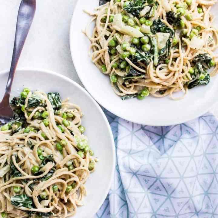 spicy tahini pasta with sauteed kale + peas + onion