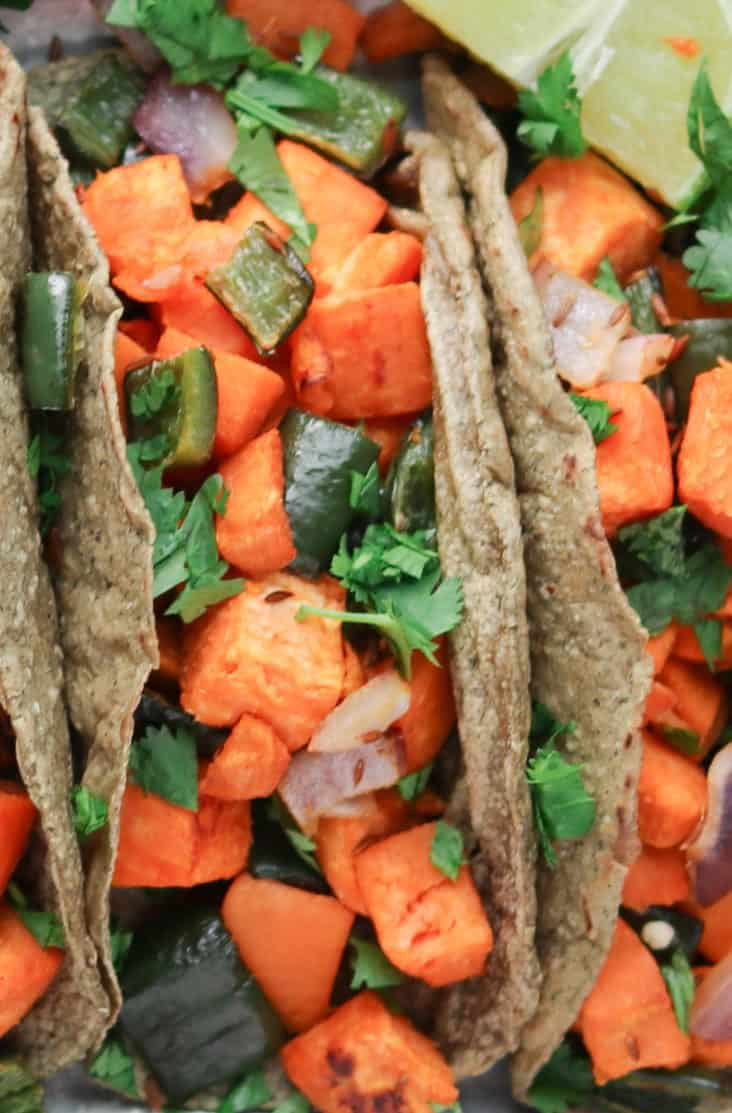 super close up of sweet potato tacos in blue corn tortilla shells with red onion, poblano pepper, lime and cilantro