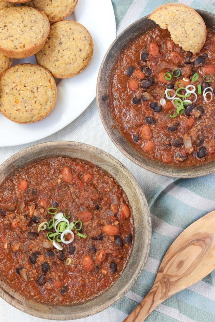 overhead shot of Best damn Vegan Chili in 2 wooden bowls and a wooden spoon with polenta muffins on a green striped towel.
