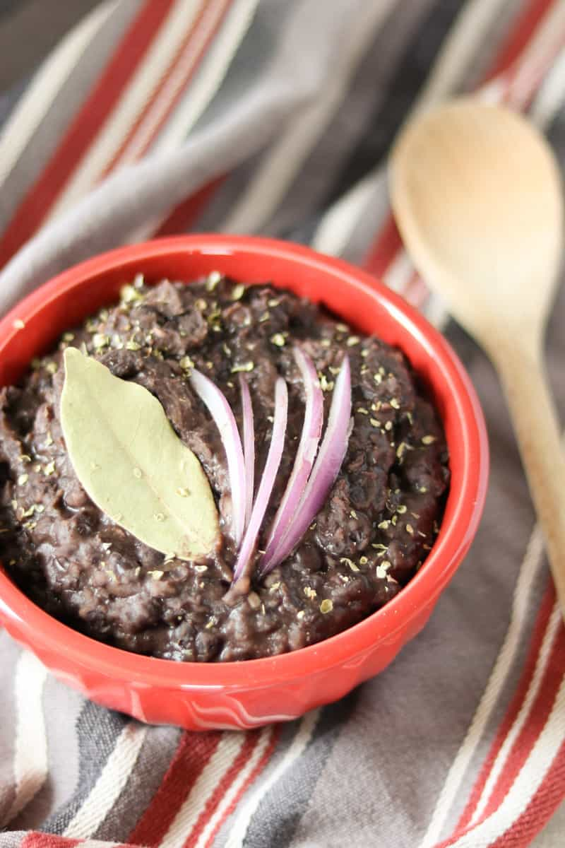 black beans, a bay leaf and red onion in a red bowl on a striped towel with a wooden spoon