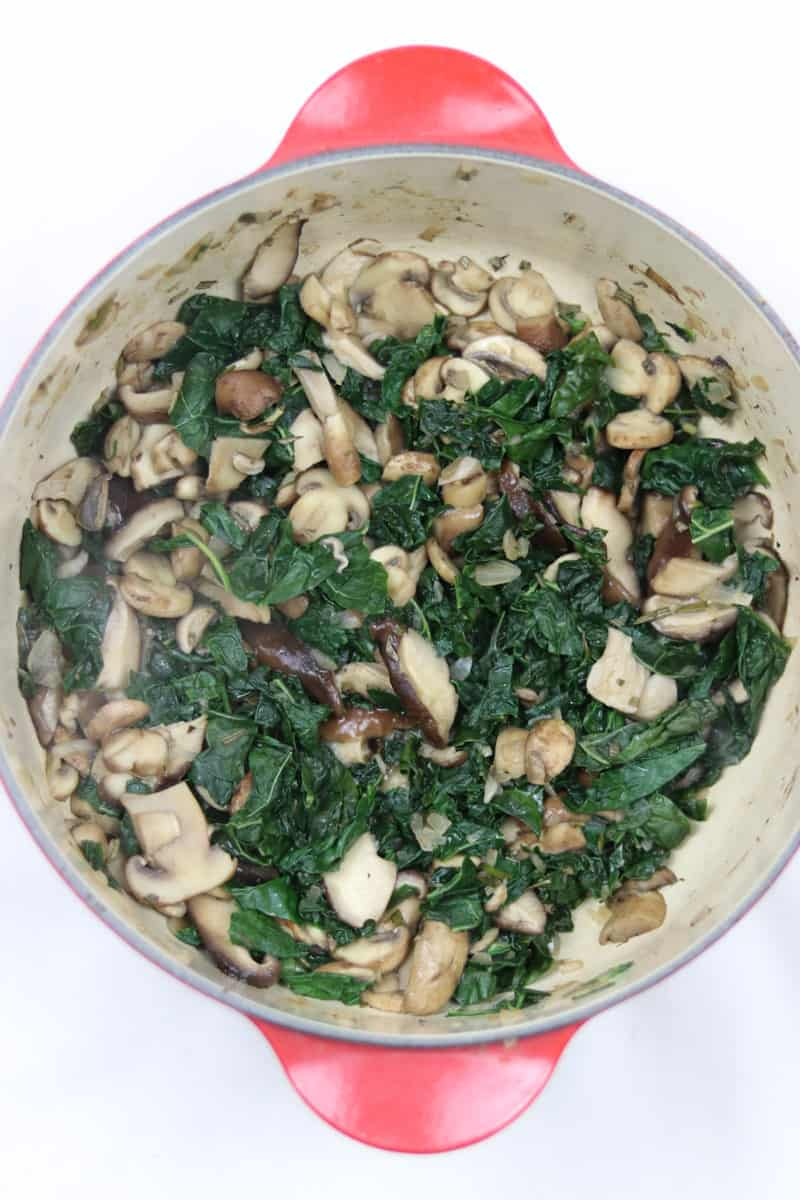 Kale and Mushrooms sautéed in a red dutch oven.