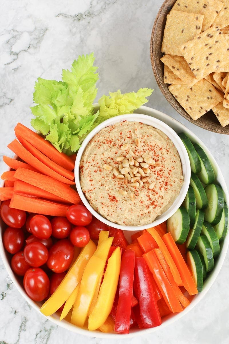Oil free hummus on a white platter with fresh sliced veggies and rice crackers