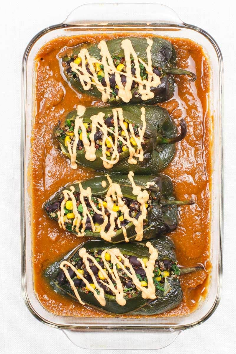 vegan chile relleno in a baking dish with red sauce and vegan cheese sauce