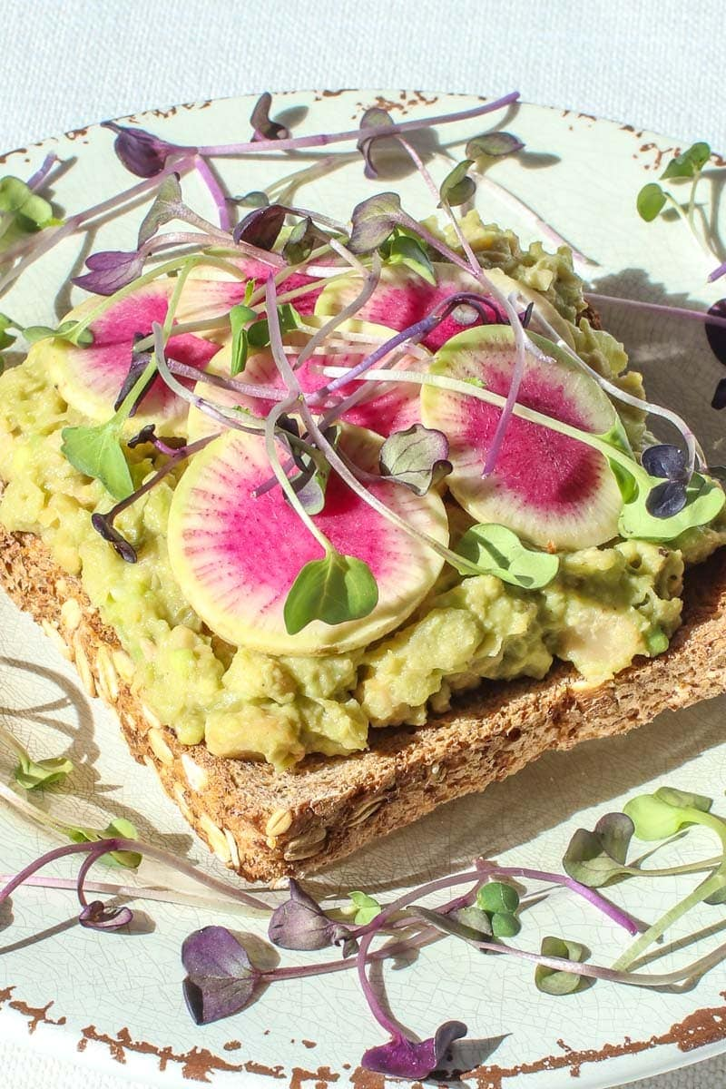 close up of vegan egg salad on toast with beauty heart radishes and micro greens on a plate