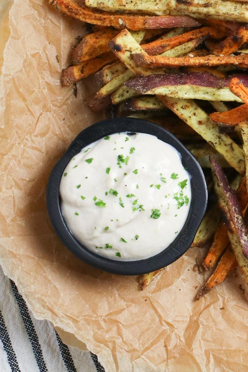 vegan oil free aioli in a black dish with baked sweet potato fries on brown parchment paper