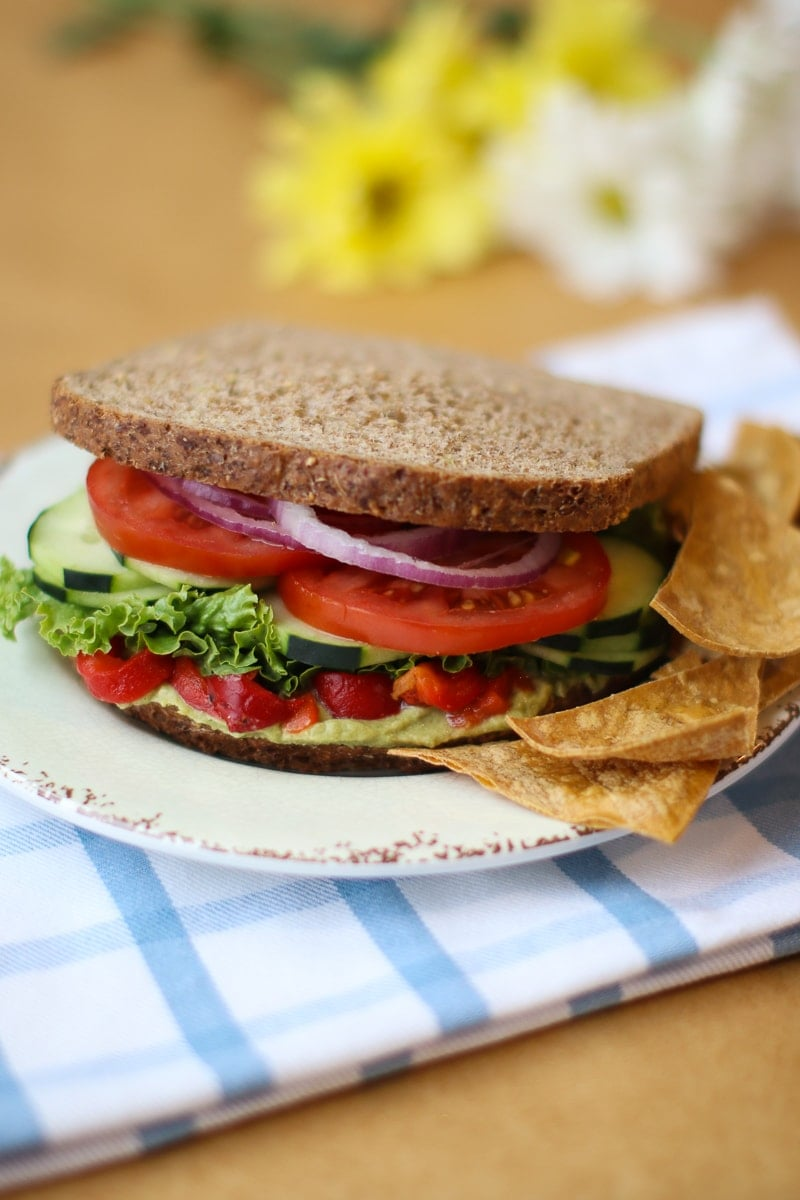 Mediterranean sandwich on a plate with tortilla chips plaid napkin and daisies
