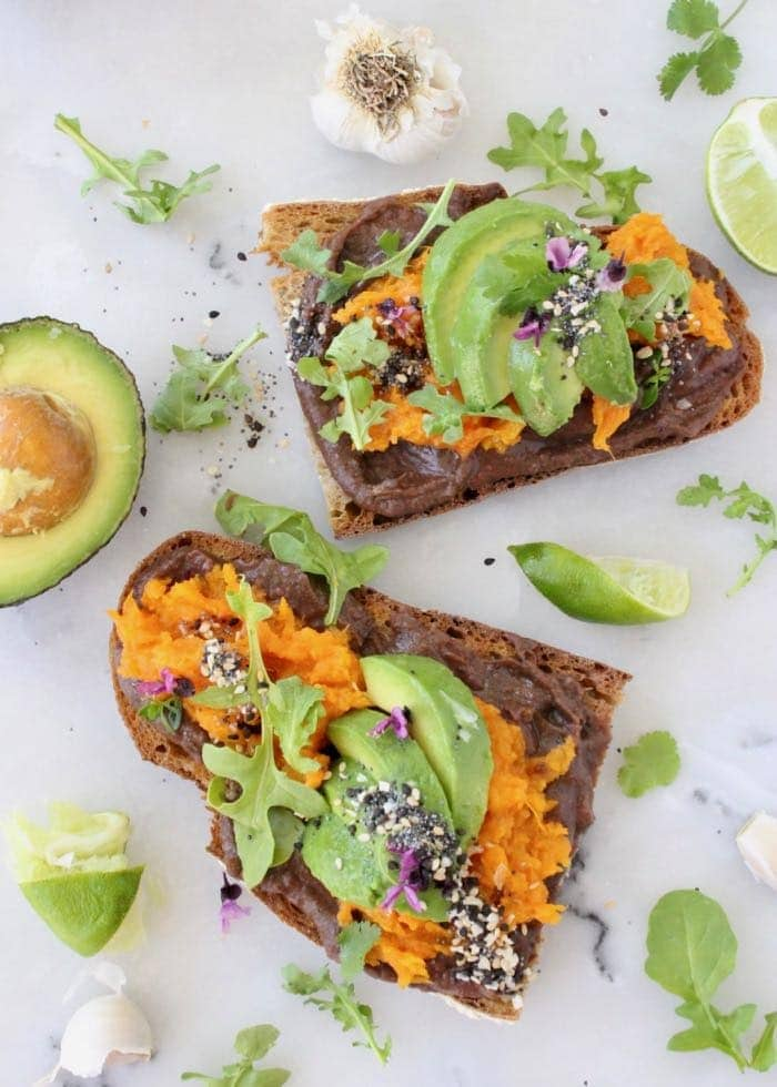 Sweet Potato Avocado Tartine on marble with arugula, surrounded by line avocado and garlic